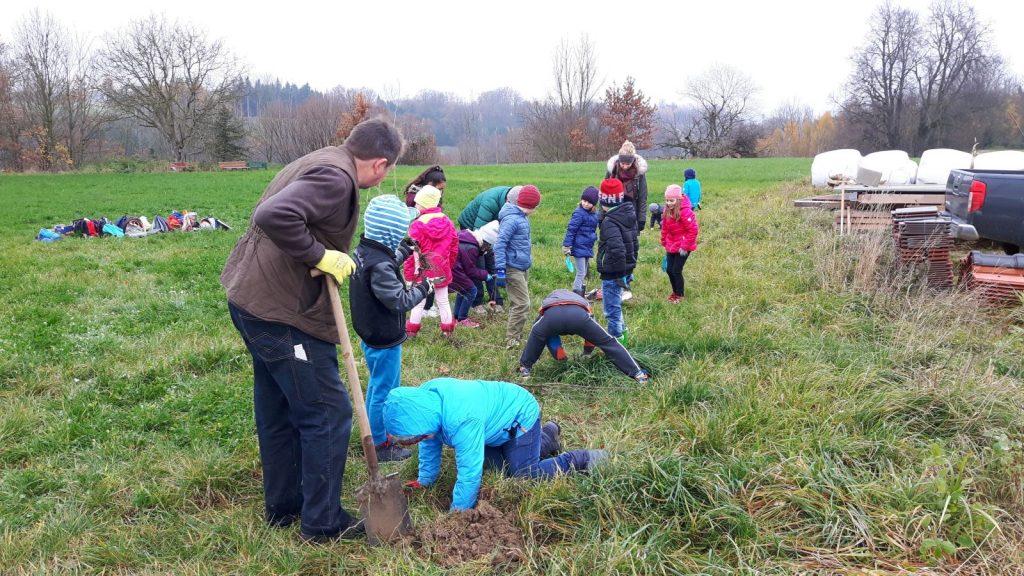 Jäger Konrad Wimmer, der seine Fläche für die Naturschutz-Aktion zur Verfügung stellt, hilft den Kindern bei den Pflanzlöchern.